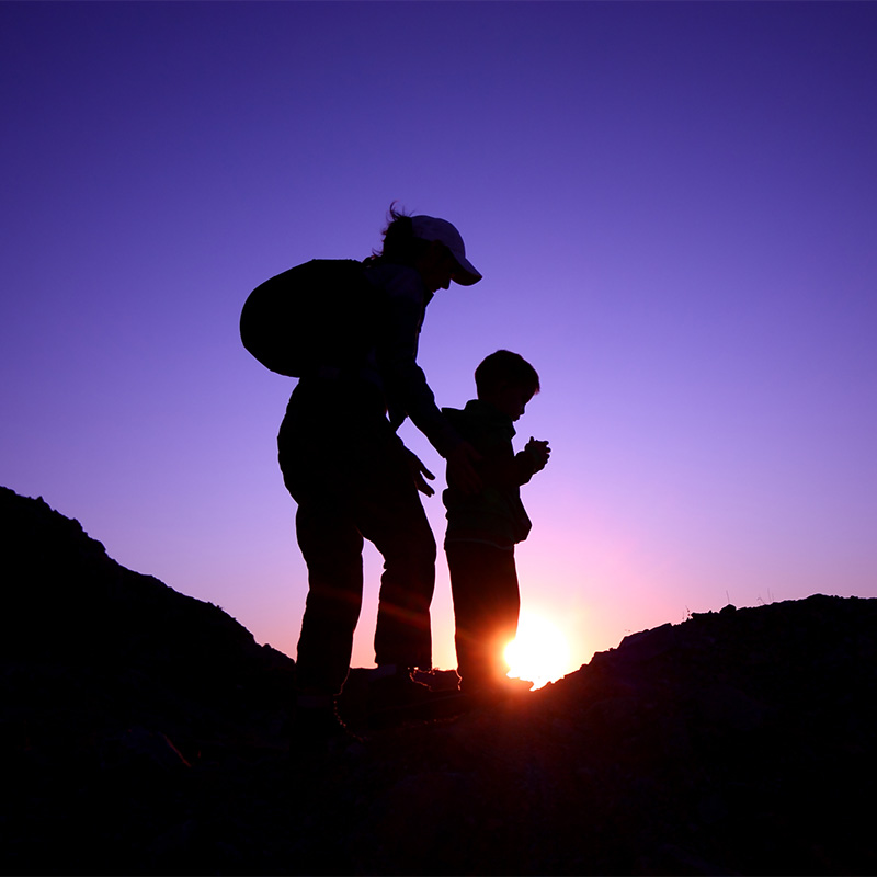 Mom and child hiking at sunset
